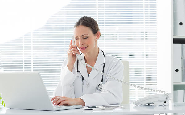 Beautiful female doctor talking on land line phone while using laptop at desk in clinic