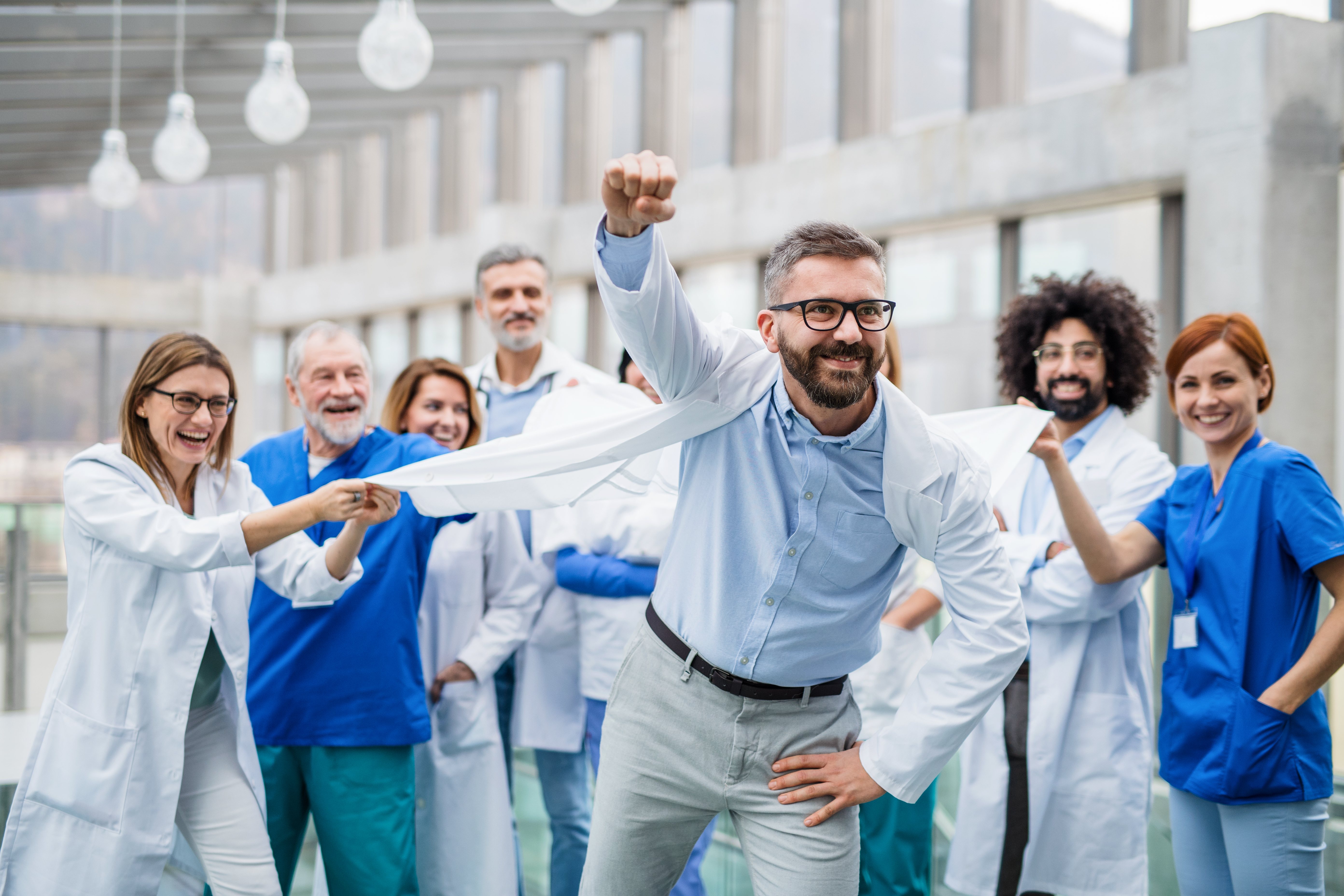 Group-of-doctors-standing-in-corridor-on-medical-conference,-having-fun.-1215473969_5568x3712